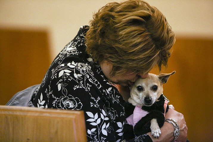 This Thursday, April 12, 2018, photo pictures a woman at a funeral home with her dog (Mike Krebs/Muskegon Chronicle via AP)