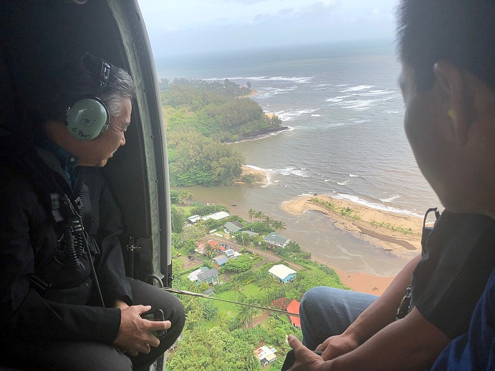In this Monday, April 16, 2018, photo provided by the Office of the Governor, Hawaii, Hawaii Gov. David Ige, left, flies over the flood-damaged areas of the island of Kauai. Heavy rains on Kauai let up on Monday, which helped emergency workers better rescue people stranded by flooding on the island. Ige were in a helicopter Monday assessing the damage and rescue needs on the island. (Courtesy of Hawaii Governor's Office via AP)