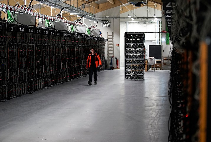 In this file photo taken on Jan. 17, 2018, a worker walks along a row of computer rigs that run around the clock 'mining' bitcoin inside the Genesis Mining cryptocurrency mine in Keflavik, Iceland. A prisoner in Iceland suspected of masterminding the theft of about 600 computers used to mine bitcoin has managed to escape custody and flee the remote North Atlantic nation on a passenger plane. Police said surveillance footage showed a suspect they identified as Sindri Thor Stefansson boarding a passenger plane to Sweden on Tuesday April 17, 2018. (AP Photos/Egill Bjarnason, File)