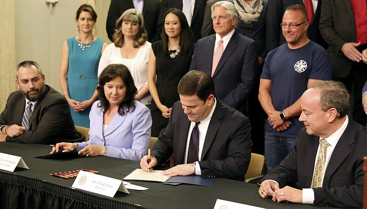 In this May 26, 2016, file photo, Arizona Gov. Doug Ducey, second from right, signs a proclamation at the state Capitol in Phoenix, certifying the results of Proposition 123 on school funding. A Phoenix man who won a federal court ruling finding Arizona distributed more than $344 million to schools since 2016 without Congressional approval won't ask for the money to be repaid because Congress finally approved the payouts last month. (Ryan Van Velzer/AP Photo)