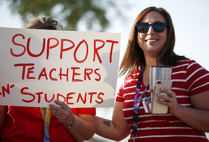 "In this April 11, 2018 photo, Stefanie Lowe, a teacher at Tuscano Elementary School, joins other teachers, parents and students as they stage a ""walk-in"" for higher pay and school funding in Phoenix. (Ross D. Franklin/AP, File)"