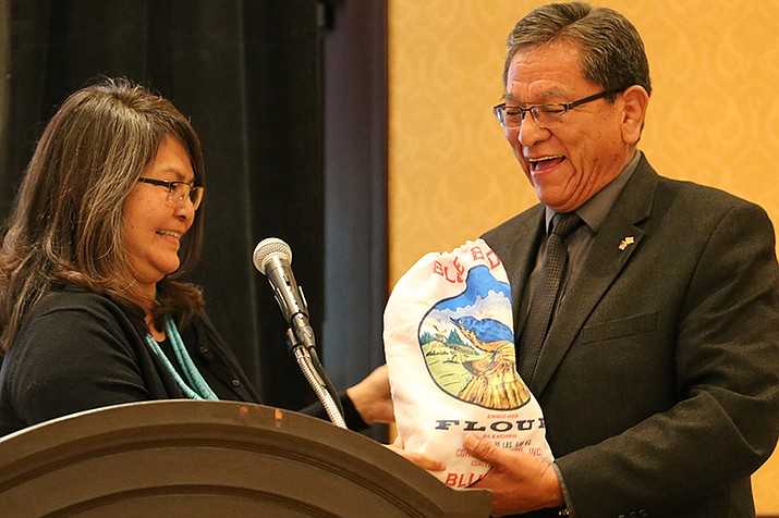 Jennifer Wheeler, education specialist for the BIE Navajo District, presents a bag of Blue Bird flour to President Russell Begaye after his speech April  6 at the Diné Language Symposium. (Navajo Nation Office of the President)