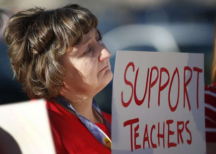 "Nanette Swanson pauses as she listens to another teacher at Tuscano Elementary School talk about the hardships of low pay as teachers, parents and students stage a ""walk-in"" for higher pay and school funding Wednesday, April 11, 2018, in Phoenix. Teachers gathered outside Arizona schools to show solidarity in their demand for higher salaries staging ""walk-ins"" at approximately 1,000 schools that are part of a statewide campaign for a 20 percent raise and more than $1 billion in new education funding. (AP Photo/Ross D. Franklin)"