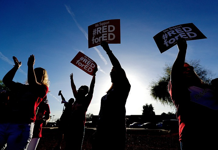 In this April 11, 2018, file photo, teachers at Humphrey Elementary school participate in a state-wide walk-in prior to classes in Chandler, Ariz. Arizona teachers began to vote Tuesday, April 17  on whether to walk off the job in their push for more funding for education. (AP Photo/Matt York, File)