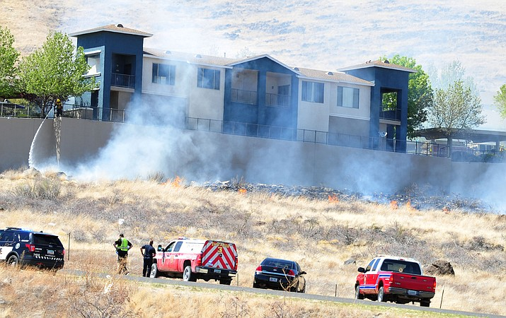 Area firefighters work to extinguish a wildfire that started near a retaining wall just below the Terraces at Glassford Hill apartment complex in Prescott Valley mid-day Wednesday, April 18.
