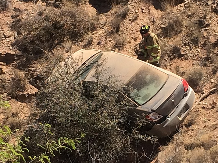 The Verde Valley Fire District firemen and Verde Valley Ambulance help pull a driver from his car which was stopped by a bush on a steep hill a half mile west of Old Town Cottonwood heading towards Clarkdale. (VVN/Vyto Starinskas.)