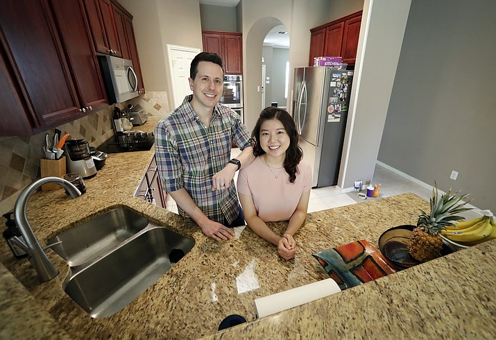 Rob Chilton and his wife Saria pose for a photo in their recently purchased home in Frisco, Texas. To cope with rising prices in Dallas, first-time buyers like Rob Chilton and his wife have broadened their search area, even if it lengthens their commutes to work. The couple, who cut back on dining out and other luxuries the past few years to set aside money for a down payment, bought a three-bedroom, two-bath fixer-upper for $335,000 in February. (Tony Gutierrez/AP Photo)