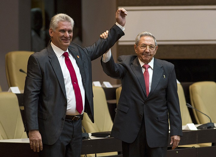 Cuba's new president Miguel Diaz-Canel, left, and former president Raul Castro, raise their arms after Diaz-Canel was elected as the island nation's new president, at the National Assembly in Havana, Cuba, Thursday, April 19, 2018. Castro left the presidency after 12 years in office when the National Assembly approved Diaz-Canel's nomination as the candidate for the top government position. (Irene Perez/Cubadebate via AP)