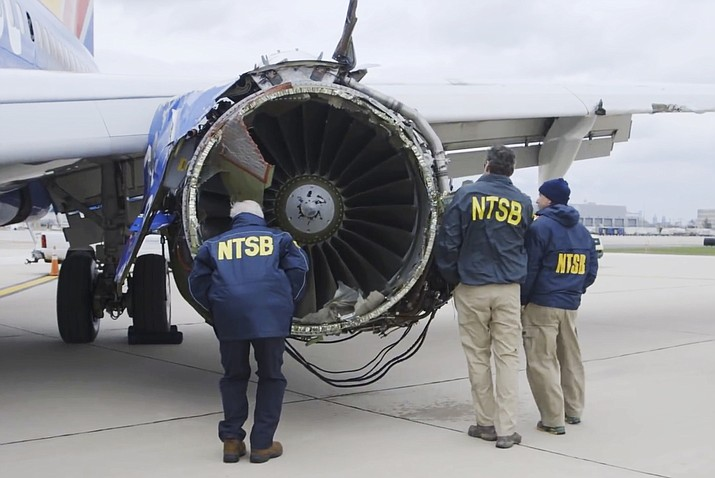 "In this Tuesday, April 17, 2018 frame from video, a National Transportation Safety Board investigator examines damage to the engine of the Southwest Airlines plane that made an emergency landing at Philadelphia International Airport in Philadelphia. A preliminary examination of the blown jet engine of the Southwest Airlines plane that set off a terrifying chain of events and left a businesswoman hanging half outside a shattered window showed evidence of ""metal fatigue,"" according to the National Transportation Safety Board. (NTSB via AP)"