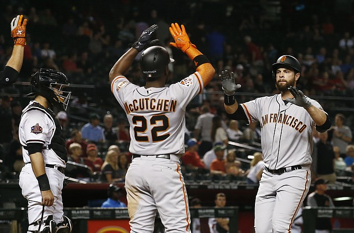 San Francisco Giants' Brandon Belt, right, celebrates his two-run home run with Andrew McCutchen (22), while Arizona Diamondbacks catcher Alex Avila, left, stands at home plate during the 10th inning of a baseball game Wednesday, April 18, 2018, in Phoenix. (Ross D. Franklin/AP)