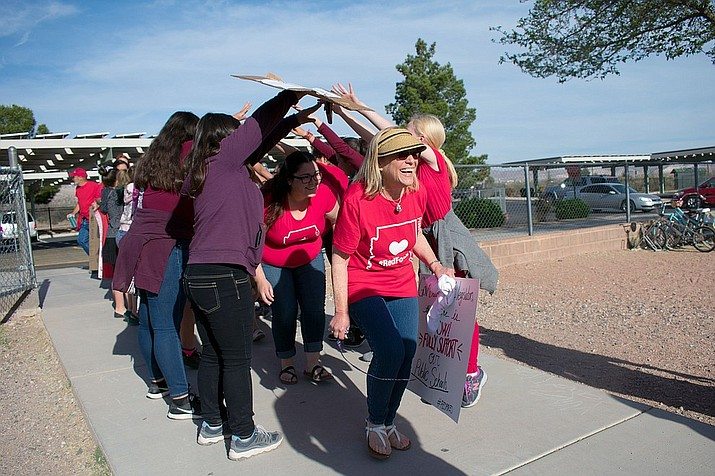 Cottonwood Elementary School faculty donned red shirts and held signs as they stood on the sidewalk on April 11 in participation of the Red for Ed walk-in. The movement is now a state-wide demand in support of Arizona schools. As faculty proceeded with the walk-in, elementary students formed an arm bridge for the teachers to walk under. (VVN/Halie Chavez)