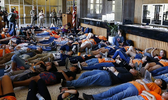 "Local high school students hold a ""die-in"" in the latest protest against gun violence at the Arizona Capitol Friday, April 20, 2018, in Phoenix. (AP Photo/Ross D. Franklin)"