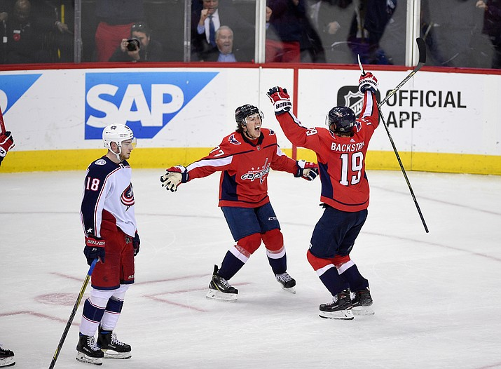 Washington Capitals center Nicklas Backstrom (19), of Sweden, celebrates his winning goal with T.J. Oshie (77) in overtime of Game 5 of an NHL first-round hockey playoff series as Columbus Blue Jackets center Pierre-Luc Dubois (18) skates by, Saturday, April 21, 2018, in Washington. (Nick Wass/AP)