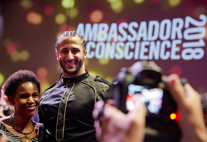 Former NFL quarterback and social justice activist Colin Kaepernick poses with guests after receiving the Amnesty International Ambassador of Conscience Award for 2018 in Amsterdam, Saturday April 21, 2018. Kaepernick became a controversial figure when refusing to stand for the national anthem, instead he knelt to protest racial inequality and police brutality. (Peter Dejong/AP)