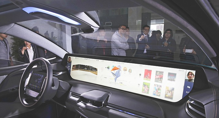 Invited guests and journalists are seen through the windshield of a BYTON electric-concept car on display during a test drive event ahead of the Auto China 2018 automotive exhibition in Beijing, Sunday, April 22, 2018. The biggest global auto show of the year showcases China's ambitions to become a leader in electric cars and the industry's multibillion-dollar scramble to roll out models that appeal to price-conscious but demanding Chinese drivers. (AP Photo/Andy Wong)