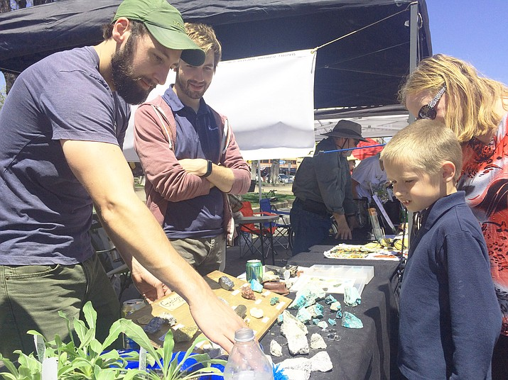 Chase Barron and Tom Haber of FreePort-McMoran Copper & Gold show Zachery and Dawn Grantham some of the geology from Bagdad at the Earth Day Celebration downtown on Saturday, April 21. (Jason Wheeler/Courier)