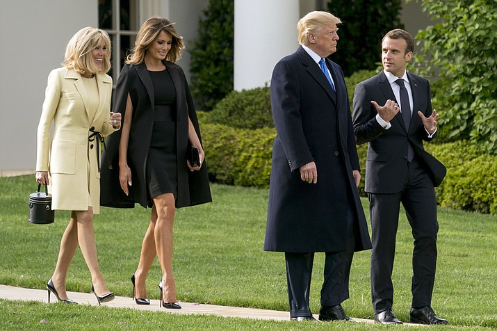 President Donald Trump and French President Emmanuel Macron, accompanied by first lady Melania Trump, second from left, and Brigitte Macron, left, talks as they walk to a tree planting ceremony on the South Lawn of the White House in Washington, Monday, April 23, 2018. (AP Photo/Andrew Harnik)