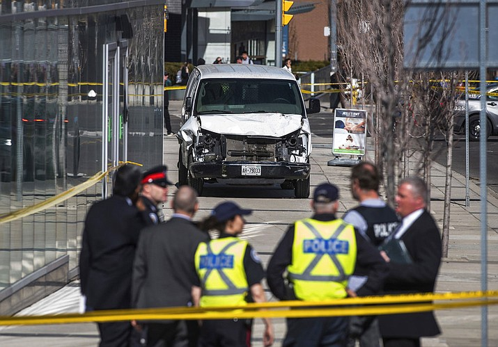 Police are seen near a damaged van after a van mounted a sidewalk crashing into pedestrians in Toronto on Monday, April 23, 2018. The van apparently jumped a curb Monday in a busy intersection in Toronto and struck the pedestrians and fled the scene before it was found and the driver was taken into custody, Canadian police said. (Aaron Vincent Elkaim/The Canadian Press via AP)