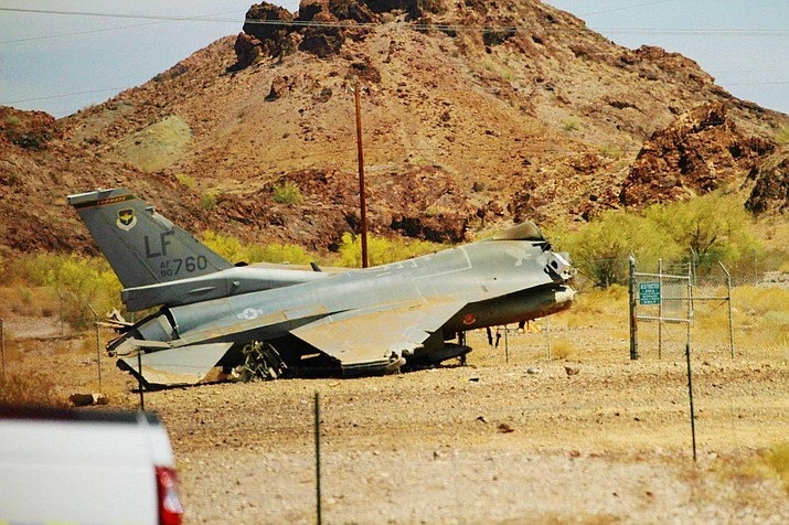 A damaged F-16 sits at the edge of the runway at the Lake Havasu City Municipal Airport Tuesday afternoon after the military jet made an emergency landing and skidded off the runway. (Brandon Messick/Today's News-Herald)
