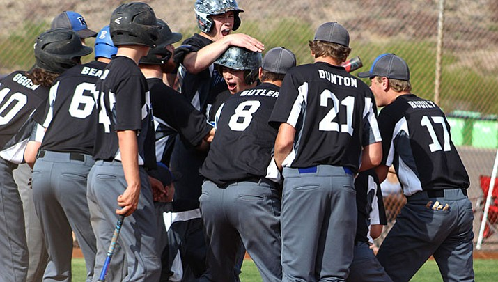 Kingman Academy's Bradley Hecker celebrates with his teammates after hitting a grand slam in the bottom of the second inning Tuesday against Parker.