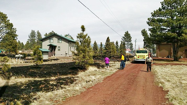 Firefighters and residents observe the aftermath of a 1.8 acre grass fire in Parks April 19. (Ponderosa Fire Dept.)