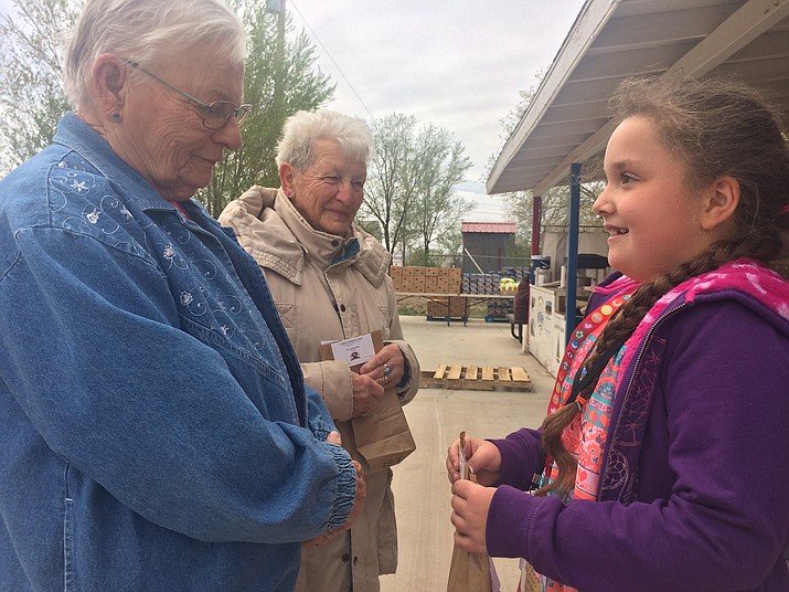 Second-grader Makayla Nelson talks with Laurel Gill and Agnes Brinson about Paulden Community School. Nelson got to be principal for an hour thanks to good grades and behavior. (Jason Wheeler/Review)