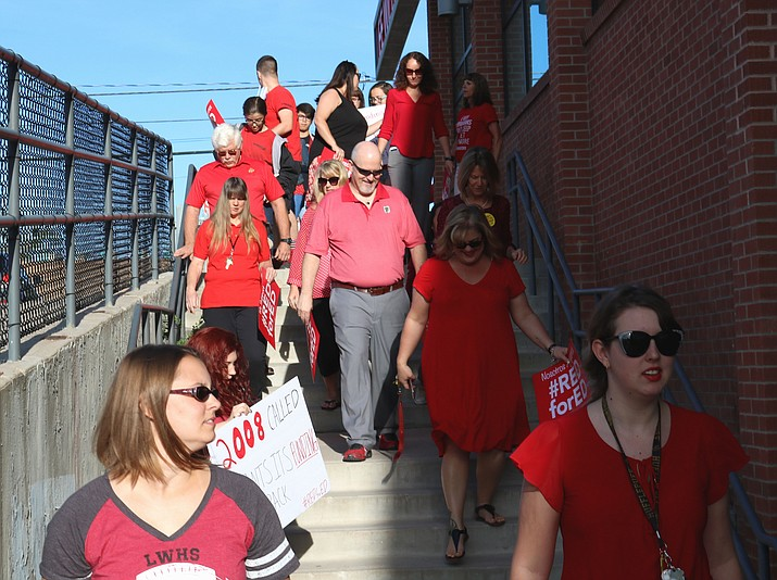 "Teachers at Lee Williams High School participated in a walk-in Tuesday morning to show that they would prefer to ""walk-in"" to school with their students, some of whom also participated."