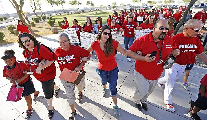 """Teachers walk arm-in-arm with students and parents into Tuscano Elementary School as they stage a """"walk-in"""" for higher pay and school funding Wednesday, April 11, 2018, in Phoenix. Teachers gathered outside Arizona schools to show solidarity in their demand for higher salaries staging """"walk-ins"""" at approximately 1,000 schools that are part of a statewide campaign for a 20 percent raise and more than $1 billion in new education funding. (AP Photo/Ross D. Franklin)"""