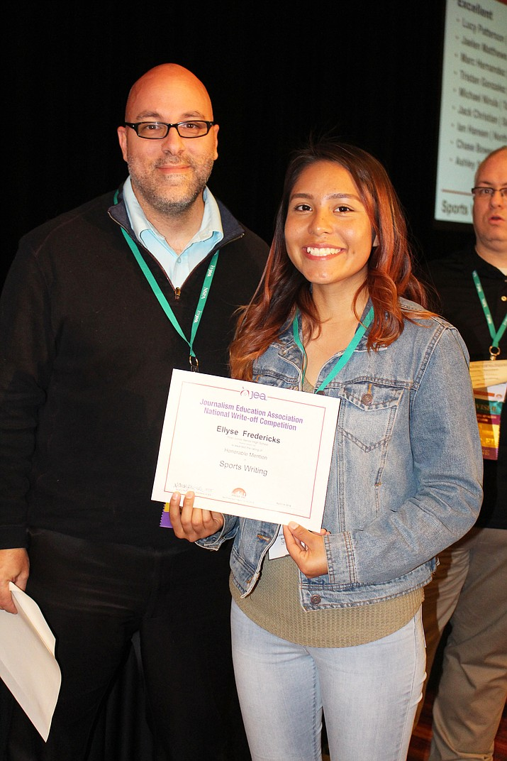 Hopi High print journalism student Ellyse Fredericks receives her national award from a Journalism Education Association official. (Stan Bindell/NHO)