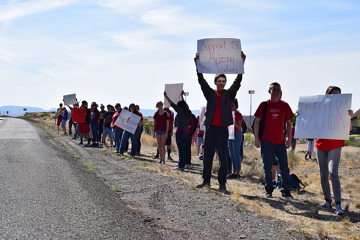 High school students hoist signs on the side of Highway 69 to grab attention for more funding to support their teachers. (Mayer Unified School District/Courtesy)