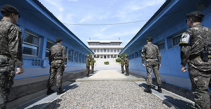 Four North Korean soldiers, center far, and four South Korean soldiers, right and left, stand at the border village of Panmunjom in the Demilitarized Zone, South Korea, Thursday, April 26, 2018. North Korean leader Kim Jong Un and South Korean President Moon Jae-in will plant a commemorative tree and inspect an honor guard together after Kim walks across the border Friday for their historic summit, Seoul officials said Thursday.(Hwang Kwang-mo/Yonhap via AP)