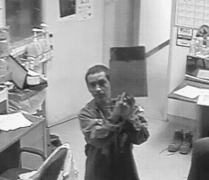A man suspected of stealing a 2015 Ford F-550 used by the Waste Management Gray Wolf Landfill on Highway 169 is shown on a camera wearing one of the company's employee uniforms and pointing to a clipboard. (Yavapai County Sheriff's Office/Courtesy)