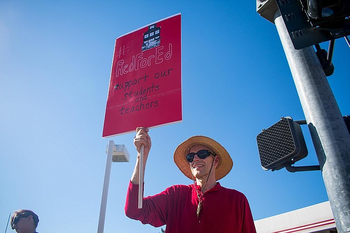 Village of Oak Creek resident and retired public school teacher Mark Bily holds up a Red for Ed sign to rally for public education funding along State Route 89A and 260 in Cottonwood on Wednesday. VVN/Halie Chavez
