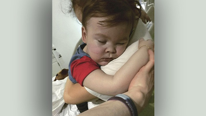 In this handout photo from April 23, 2018, provided by Alfie's Army Official, brainwrecked toddler Alfie Evans caresses his mother Kate James at Alder Hey Hospital in Liverpool, England. Kate James and Tom Evans, the parents, said on Facebook that 23-month-old Alfie Evans, who had an incurable degenerative brain disease and was at the center of litigation over his treatment, died in the early morning of April 28, 2018. (Alfie's army officer via AP)