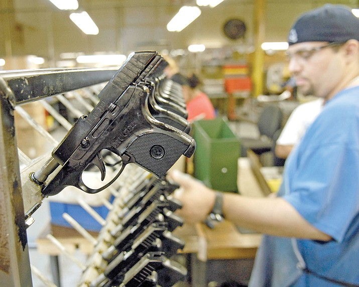 Dirkson Davis, lead assembler at Ruger, completes each pistol and places the Light Compact Pistol on a rack for the next phase of production. Manufacturing jobs are on the rise in the tri-city area with the economy also on the rise. (Courier file photo)