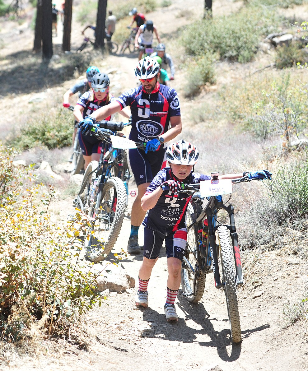 10-year old Chase Milham leads his family up from the Sierra Prieta overlook during the Whiskey Off Road 30 and 50 mile amateur races in Prescott Saturday, April 28, 2018. (Les Stukenberg/Courier)