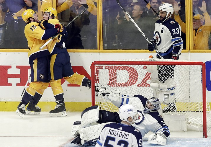 Nashville Predators left wing Kevin Fiala, second from left, of Switzerland, celebrates with Craig Smith (15) as Winnipeg Jets defenseman Dustin Byfuglien (33) skates by after Fiala scored the winning goal during the second overtime in Game 2 of an NHL hockey second-round playoff series, Sunday, April 29, 2018, in Nashville, Tenn. (Mark Humphrey/AP)