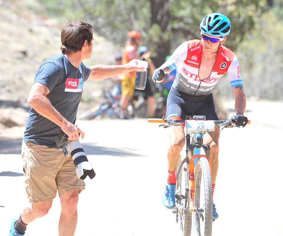 Keegan Swenson gets a new bottle from Kenny Wehn during the Whiskey Off Road  50 mile professional race in Prescott Sunday, April 29, 2018. (Les Stukenberg/Courier)