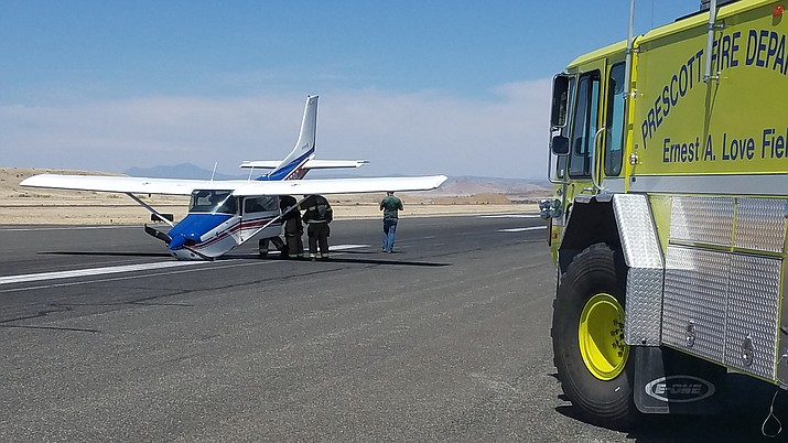 Prescott Fire Department firefighters assist the passengers of a Cesna airplane exit the aircraft after it crash landed at the Prescott Municipal Airport Sunday afternoon, April 29.