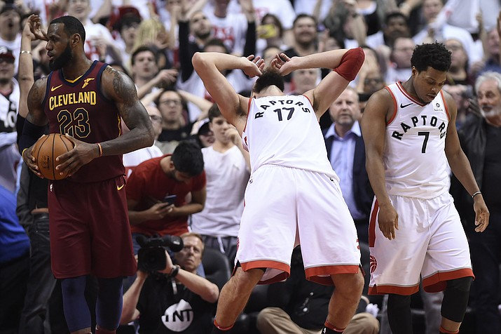 Toronto Raptors center Jonas Valanciunas (17) and guard Kyle Lowry (7) react after Valanciunas missed a shot late in the second half second, as Cleveland Cavaliers forward LeBron James (23) holds the ball during Game 1 of an NBA basketball playoffs Eastern Conference semifinal, Tuesday, May 1, 2018, in Toronto. (Nathan Denette/The Canadian Press via AP)