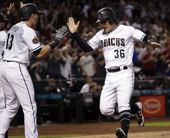 Arizona Diamondbacks' John Ryan Murphy (36) high-fives Nick Ahmed (13) after scoring on a two-run triple by Daniel Descalso during the seventh inning of a baseball game against the Los Angeles Dodgers on Tuesday, May 1, 2018, in Phoenix. (AP Photo/Matt York)