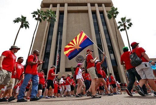 Teachers rally outside of Arizona Gov. Doug Ducey's Executive Tower Monday, April 30, 2018, in Phoenix on their third day of walk outs. (AP Photo/Matt York)