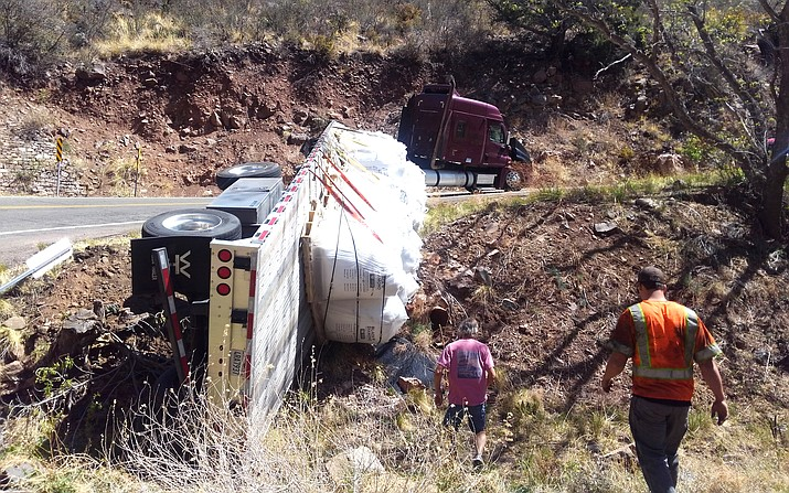 Once on-scene, Jerome Fire found a tractor trailer blocking the Northbound lane of SR 89A with the trailer on its side in a 10-foot ravine, still attached to the truck. There were five wheels suspended about five feet off of the ground with the 40,000-pound load of copper slag in bags that were spilling into the wash. Photo courtesy of Ron Chilston/Jerome Fire Dept.