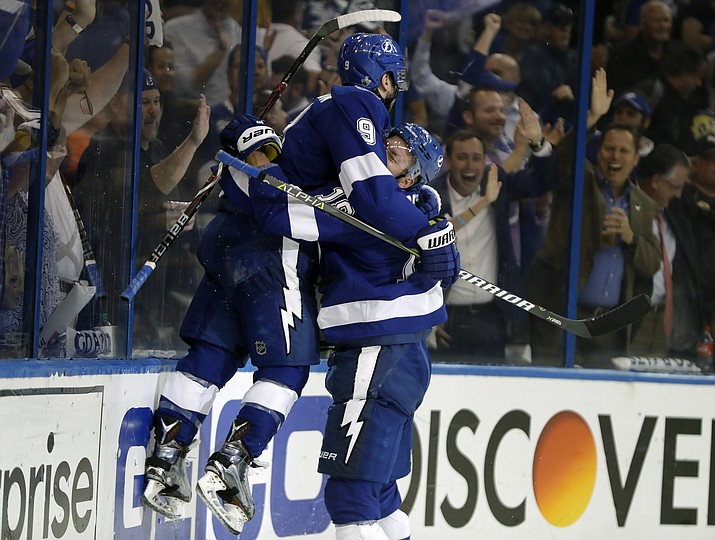 Tampa Bay Lightning center Tyler Johnson (9) gets lifted off the ice by left wing Ondrej Palat (18) after Johnson scored against the Boston Bruins during the second period of Game 2 of an NHL second-round hockey playoff series Monday, April 30, 2018, in Tampa, Fla. (AP Photo/Chris O'Meara)