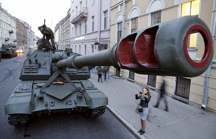 A woman takes a photo of the Self-propelled artillery vehicle Msta S prior to a rehearsal for the Victory Day military parade which will take place at Dvortsovaya (Palace) Square on May 9 to celebrate 73 years after the victory in WWII, in St.Petersburg, Russia, Monday, April 30, 2018. (AP Photo/Dmitri Lovetsky)