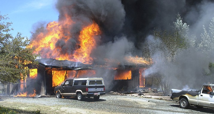 Early stages of a fire engulfs a garage and continues to spread to the adjoining home. (Courier, file)