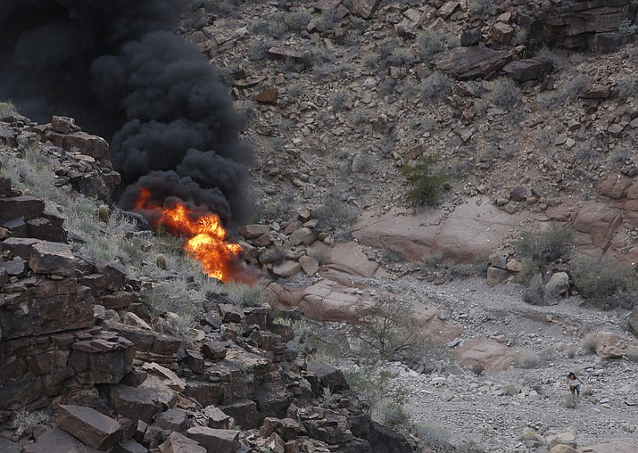 In this Saturday, Feb. 10, 2018, file photo, a survivor, lower right, walks away from the scene of a deadly tour helicopter crash along the jagged rocks of the Grand Canyon, in Arizona. Autopsies from a fiery helicopter crash at the Grand Canyon earlier this year show two British tourists aboard died of smoke inhalation and burns that covered 100 percent of their bodies. The Mohave County Medical Examiner's Office released autopsy reports Wednesday, May 2, 2018, for 27-year-old Rebecca Dobson and 31-year-old Jason Hill. They died at the scene, along with Hill's brother, 30-year-old Stuart Hill. (Teddy Fujimoto via AP,File)