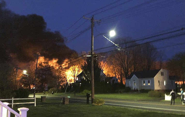 This photo provided by WFSB-TV shows a fire behind a house, Wednesday, May 2, 2018, in North Haven, Conn. A Connecticut woman's call to police to report domestic violence led to a standoff and explosion in a barn behind her home that left at least one person dead and other officers injured, officials said Thursday. (Kevin Galliford/WFSB-TV via AP)