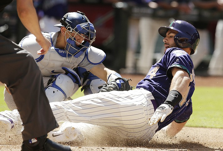 Arizona Diamondbacks Paul Goldschmidt scores in front of Los Angeles Dodgers catcher Austin Barnes during the sixth inning during a baseball game Thursday, May 3, 2018, in Phoenix. (Rick Scuteri/AP)