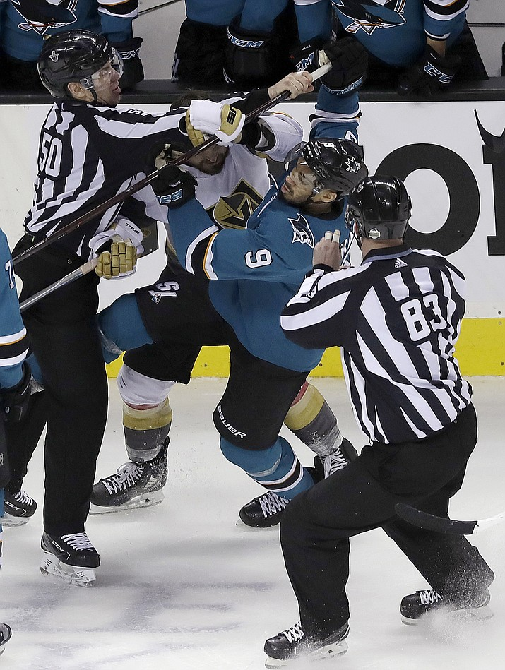 Referees try to separate San Jose Sharks left wing Evander Kane (9) and Vegas Golden Knights left wing William Carrier during the third period of Game 4 of an NHL hockey second-round playoff series in San Jose, Calif., Wednesday, May 2, 2018. The Sharks won 4-0. (AP Photo/Jeff Chiu)